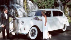 Image of bride and groom taking their wedding pictures on an antique Rolls Royce