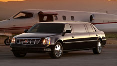 Image of black 8-10 passenger Lincoln Town Car stretch limousine next to a private airplane