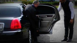 Image of chauffeur opening the door of a black CT Lincoln Town Car